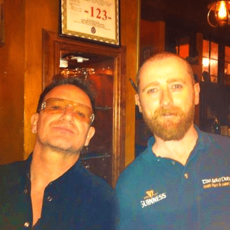 Bono of U2 pours pints for patron at Auld Dubliner in Long Beach, CA
